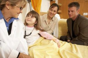 A doctor sits at the bedside of a young girl in a hospital bed while her parents look on